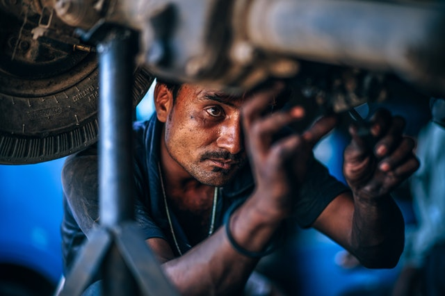 automechanik opravujúci auto