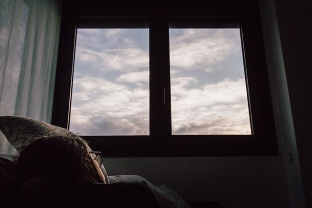 Žena s okuliarmi ležiaca pod veľkým oknom s výhľadom na oblohu.jpg