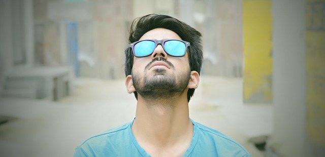 Muž v modrých okuliaroch a v modrom tričku pozerá dohora