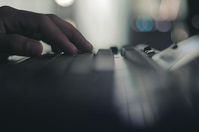 Človek ťuká do bielej klávesnice