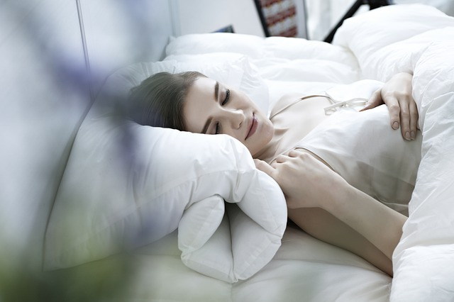 Žena v bielej nočnej košeli spí v posteli