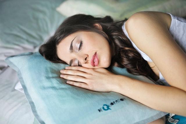 Dievča s dlhými čiernymi vlasmi spí na vankúši