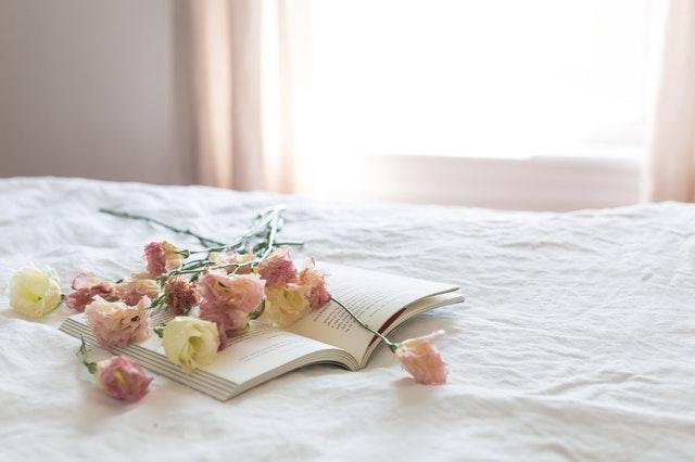 Posteľ s kvetmi a knihou